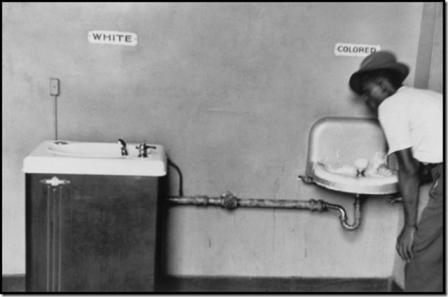 NORTH CAROLINA—A black man drinks at segregated water fountains, 1950. © Elliott Erwitt.jpg